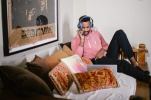 A man wears headphones while sitting on a large couch with many throw pillows, watching his laptop screen